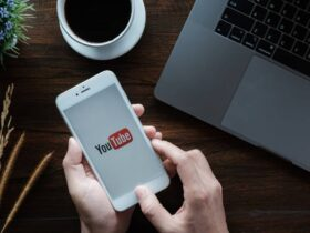 Person holding a smartphone showing Youtube logo onscreen by the wooden desk with a cup of coffee and an open laptop.